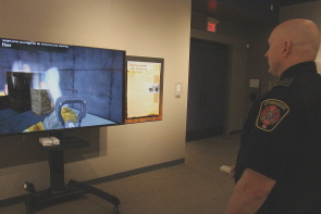Dana Terry plays  the Wii firefighter game which is part of We Are Here To Serve: Fire and EMS. Photo by Richard Amery