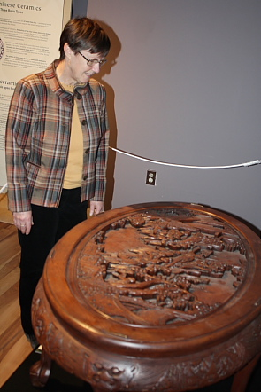 Wendy Aitkens examines an intricately carved table. Photo by Richard Amery