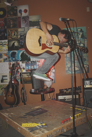 Greg Rekus jumps at the Owl Acoustic Lounge. Photo by Richard Amery