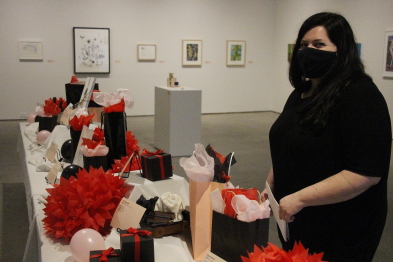 SAAG Executive director Kristy Trinier shows off some of the gift packages available to bid on during Art Frenzy. Photo by Richard Amery