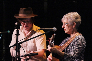 Steve Foord helps set the stage for Cathy Hawley, who placed second in this year's South Country Fair Songwriting competition at the Slice, Sunday, May 27. Photo by Richard Amery