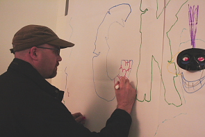 Artist Aaron Hagan adds to CKXU's mural at Synesthesia, Oct. 29. Photo By Richard Amery